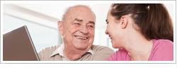 Mujer ayudando a un hombre mayor a hacer una búsqueda en Internet