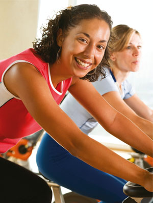 Two Women in the gym on a bicycle